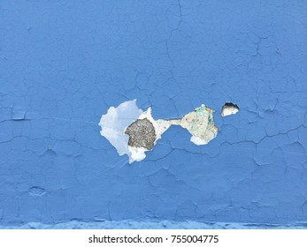 Blue paint peeling from a wall revealing white concrete texture