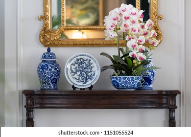 Blue paint porcelain collection with Orchid vase on a dark wooden table with golden mirror on white wall.