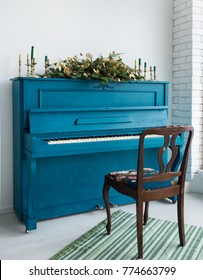 Blue painted old piano decorated with long Christmas garland and candles for holiday celebration. Golden elements of festive decor. Vertical color photo.
