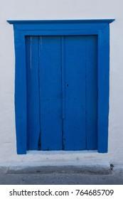 Blue painted wooden door of white building in Santorini, Greece