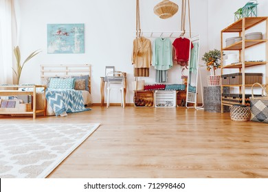 Blue painting above king-size bed with blue coverlet in bedroom with boho wardrobe in modern interior