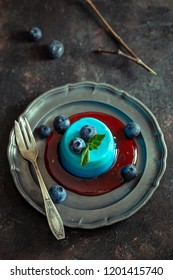 Blue panna cotta with blueberry and mint above