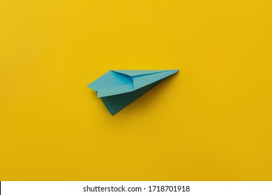 Blue paper airplane on yellow background