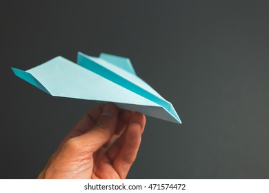 Blue paper airplane origami in hand against dark background