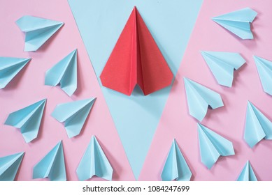 blue paper airplanes surrounding the bigger red paper airplane on pastel pink and blue color background. leadership concept