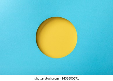 blue paper background with minimalistic yellow round hole