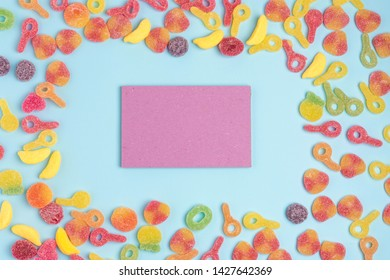 Blue paper background with sugary jellies and blank notepad. Place for your text. Cozy sweet background