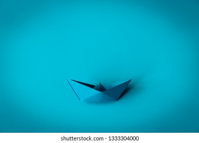 blue paper boat on blue textured background with copy space, learning and education concept