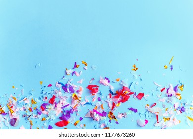 Blue paper with bright confetti top view. Copy space.