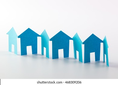 Blue paper houses in a row on white background