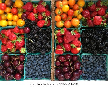 Blue paper produce boxes with assorted fruits at farmer's market: cherry tomatoes, strawberries, blackberries, cherries, blueberries. Small areas of white box background are visible around edges.