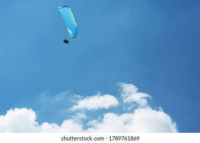 Blue Paraglider flying into the sky with clouds on a sunny day