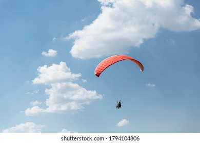 Blue Paraglider flying into the sky with clouds in a sunny day