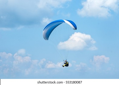 Blue paraglider flying in the blue sky against the background of clouds. Paragliding in the sky on a sunny day.