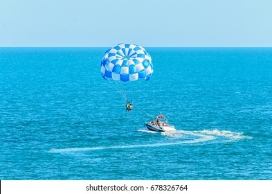 Blue parasail wing pulled by a boat in the sea water, Parasailing also known as parascending or parakiting.