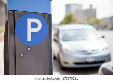 Blue parking sign with blurred cars at the background in New York City