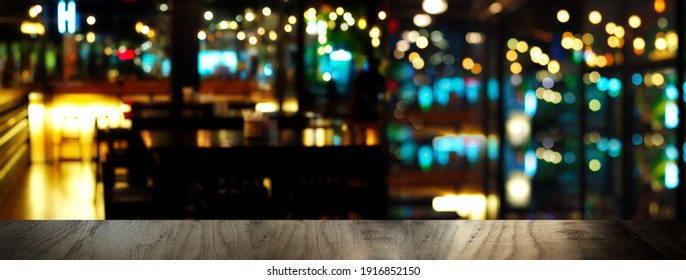 blue party glowing light and black wood table in pub or bar in Christmas night banner background