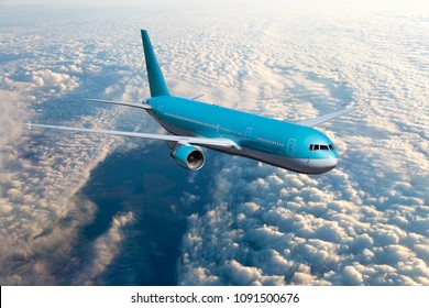 Blue passenger plane in flight. Airplane fly high above the clouds. Front view of aircraft.