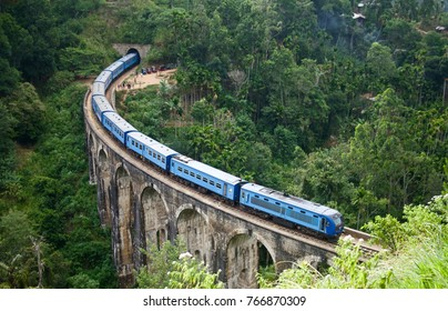 Blue passenger train in the Hill Country of Sri Laka. The train is crossing over the Nine Arch Bridge near the touristy town of Ella