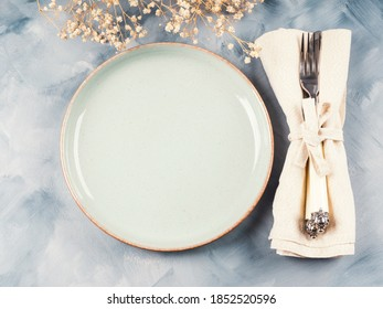 Blue pastel dish and silverware with dried flowers. Autumn table setting