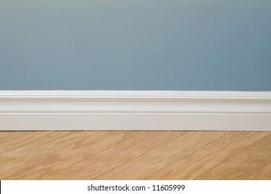 Blue pastel wall, baseboard and hardwood flooring