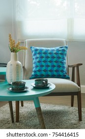 Blue pattern pillow on vintage style chair and table in living room