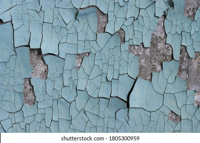 Blue peeling paint on the wall. Old concrete wall with cracked flaking paint. Weathered rough painted surface with patterns of cracks and peeling. High resolution texture for background and design.