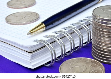 Blue pen, notebook and russian coins