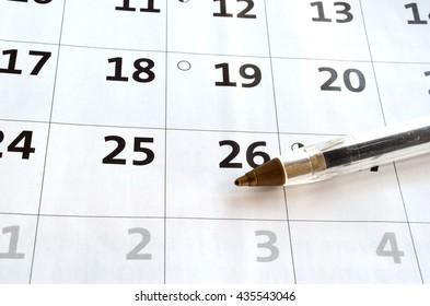 blue pen resting on a white blank calendar