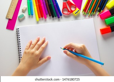 blue pencil in children's hands and a white notebook. background of pencils, felt-tip pens
