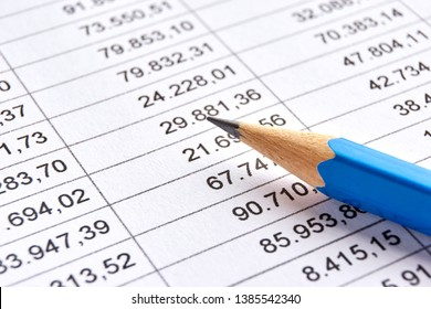 Blue pencil on a sheet of white paper with printed financial numerical data table with columns. Concept for accounting, budget, profit, tax and financial review. Image with selective focus