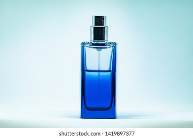 Blue perfume glass bottle on light blue background. Eau de toilette. Eau de parfum. Beautiful composition of blue perfume bottle