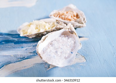Blue persian, lemon and red chili sea salt in sea shell oyster on blue abstract painted background
