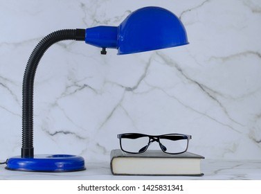A blue personal sized desk lamp on a marble desk in front of a marble wall with a book and reading glasses underneath. Good image for study, reading or back to school.