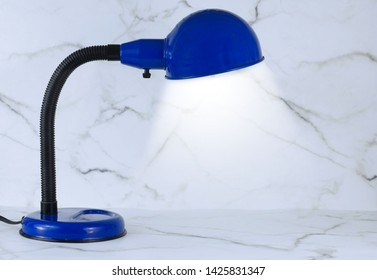 A blue personal sized desk lamp on a marble desk in front of a marble wall. The lamp appears to be lit, ready for anything to be placed underneath its' glow.