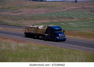 A blue peterbilt pulls a loaded flatbed down the highway. June 20th, 2017 Oregon, USA