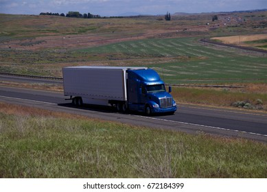 A blue Peterbilt pulls a white unmarked trailer along a rural Highway. June 20th, 2017 Oregon, USA