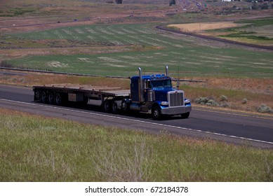 A blue Peterbilt semi-truck pulls an empty flatbed trailer. June 20th, 2017 Oregon, USA