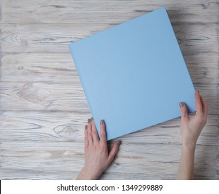 blue photo book with  leather cover.  stylish wedding photo album. a person opens a photobook. Family photoalbum. the womans hand holding a family photo album