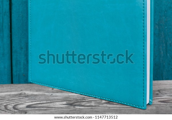 blue photobook with leather cover. Family Photo book on a bright background. wedding photo album  with bright leather cover. Photo album on a wooden surface.