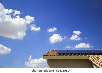 Blue photovoltaic solar panels on a residential houseâ??s rooftop