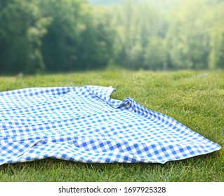 Blue picnic towel cloth on green grass background,Empty space food advertisement backdrop.Tablecloth easter backdrop.