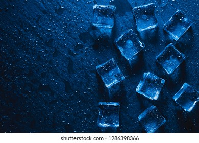 blue Pieces of ice cubes with water droops on black background. advertising photo