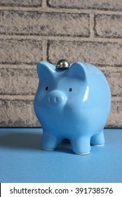 A blue pig bank rests up against a brick wall in this banking theme.