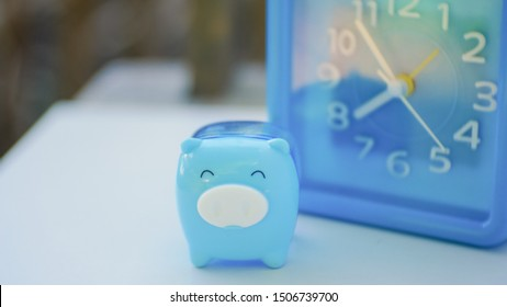 Blue pig and blue clock in saving money concept.