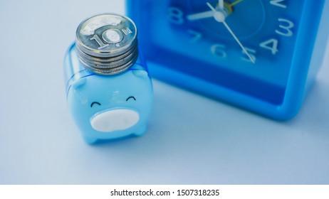 Blue pig and blue clock saving money concept.