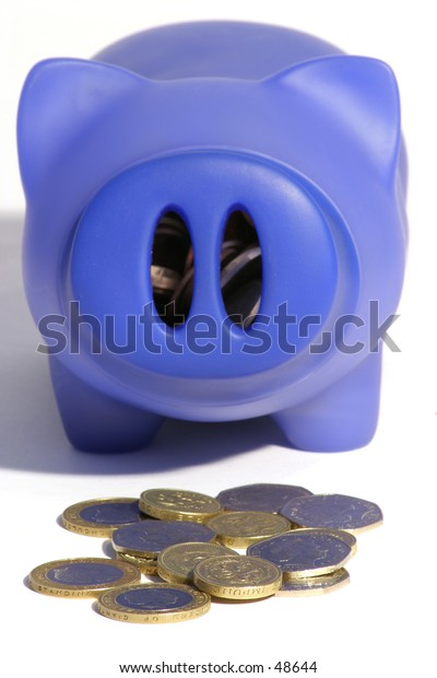 A blue pig money box with coins in front and inside.