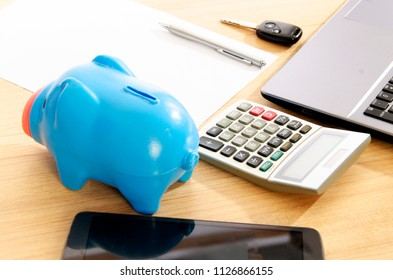 Blue piggy bank andcalculator and office supplies on wood table desk backgrounds