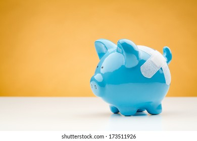 A blue piggy bank with a bandage standing on a white desk surface with an orange background.