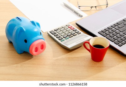 Blue piggy bank with calculator on work table desk with red cup coffee